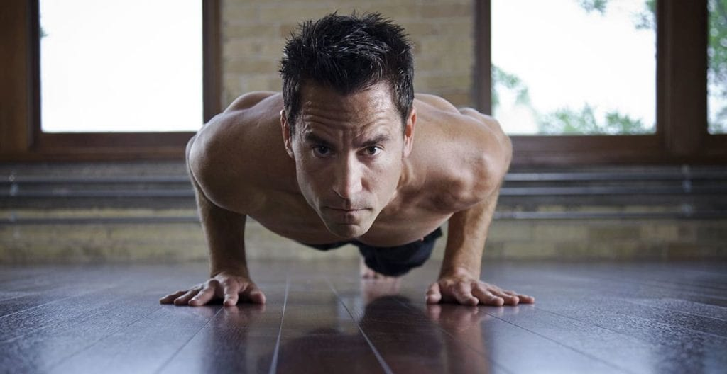 Sweaty-fit man doing HIIT yoga