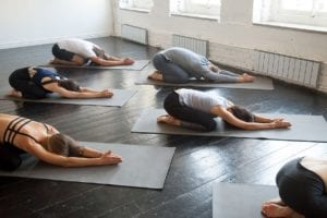 Group of young sporty people practicing in bikram yoga classes with instructor, lying in half tortoise pose