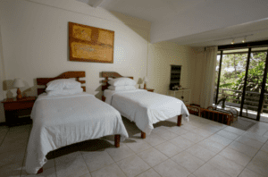 Pura Vida Spa Tri-level picture of two twin beds on first level, sitting area on second level and leading out to balcony overlooking valley on third level at yoga retreat in Costa Rica