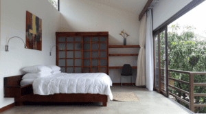 Pura Vida Spa Prana Room View of king size bed with open balcony windows overlooking forest canopy at yoga retreat in costa rica