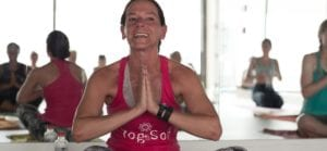 Teacher in YogaSol Tank in prayer position smiling and saying namaste after hot hiit class
